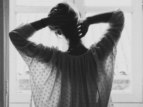 Donna di spalle davanti ad una finestra che si alza i capelli sopra la testa